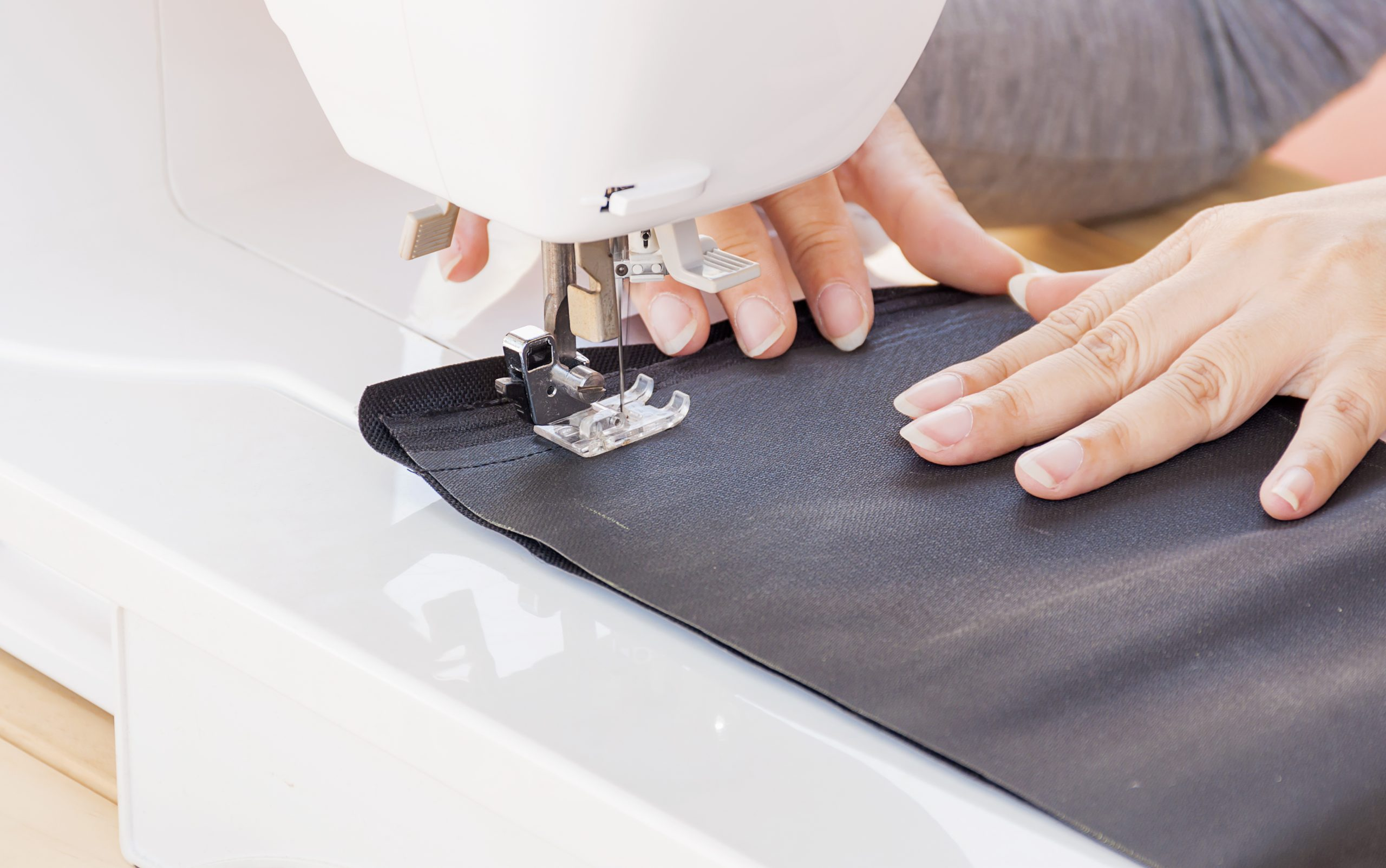 Woman's hands, doing her patchwork using sewing machine