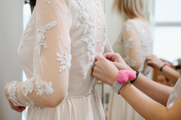 woman-with-dressmaker-making-final-touch-bridal-clothing-shop_99692-527